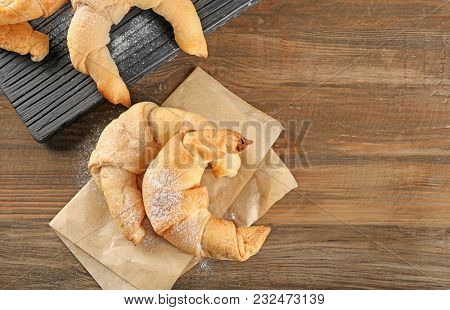 Tasty crescent rolls on wooden table