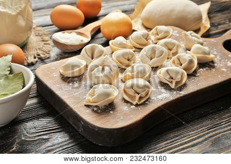 Wooden board with raw dumplings and products on table