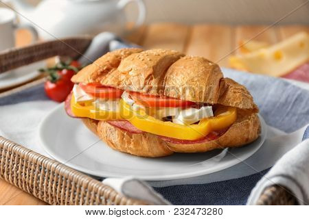 Plate with tasty croissant sandwich on tray, closeup