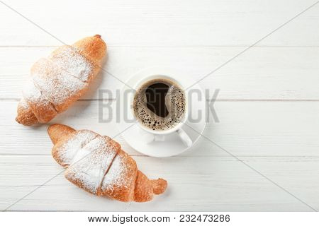Tasty croissants and cup of coffee on wooden table