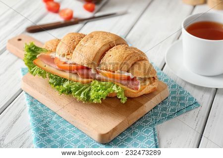 Tasty croissant sandwich on wooden board