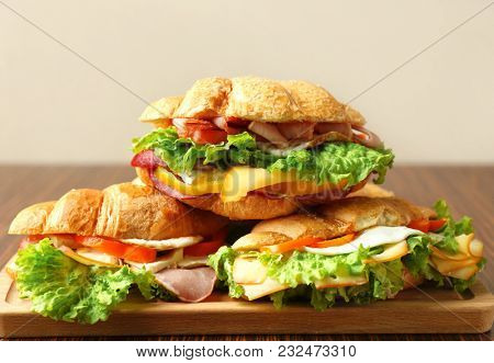 Tasty croissant sandwiches on wooden board, closeup