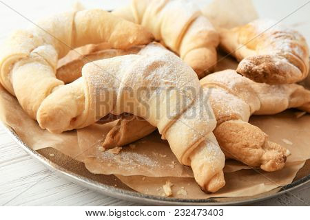 Tasty crescent rolls on plate, closeup