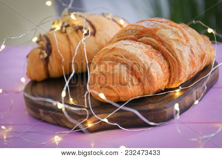 Tasty croissants with garland on wooden board