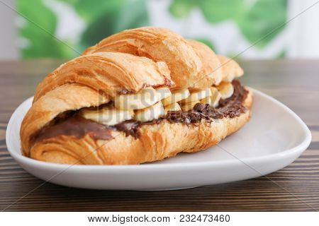 Tasty croissant with banana and chocolate sauce on plate, closeup
