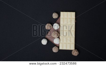 Stack Of Black And White Chocolate Isolated On Black Background, Top View With Copyspace For Your Te