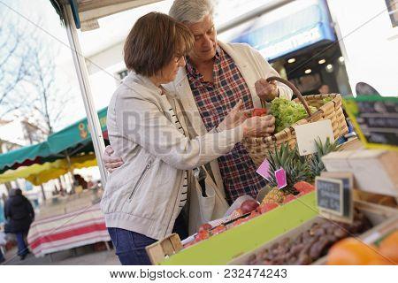 Senior couple buying fresh food at the green market