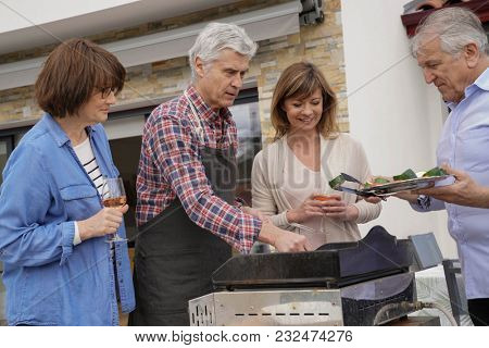 Senior people having fun cooking barbecue grill for lunch