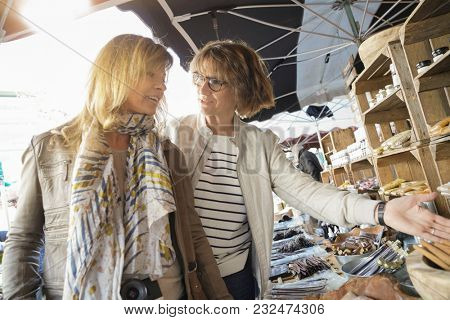 Women on vacation walking in outdoor market
