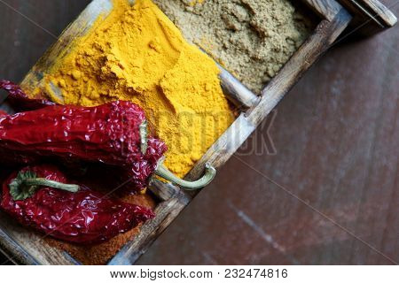 Close Up Of Indian Spices Of Turmeric Powder, Coriander Powder And Chili Powder In  A Wooden Box Wit