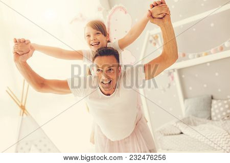 My Girl. Happy Delighted Positive Man Laughing And Having Fun With His Daughter While Playing With H