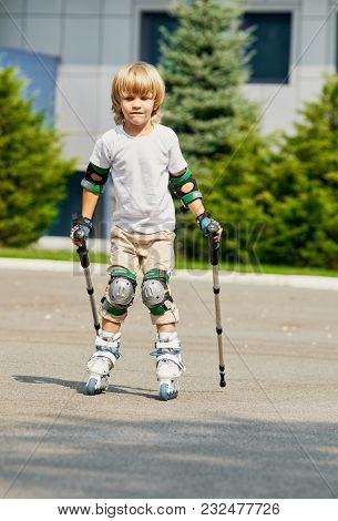 Little Boy Learning To Roller Skate And Wearing Protection Elbow And Knee Pads