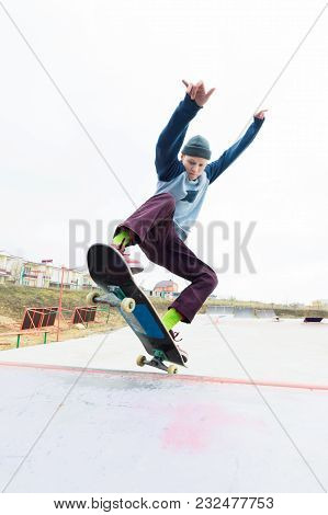 A Skateboarder Teenager In A Hat Does A Trick With A Jump On The Ramp. A Skateboarder Is Flying In T