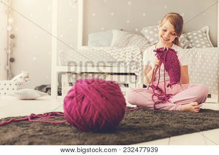 Relaxing Hobby. Happy Delighted Cute Girl Sitting At Home And Knitting A Scarf While Relaxing