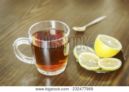 On The Surface Of The Table In A Glass Cup Hot Strong Tea And Lemon.