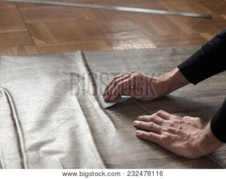 Closeup Of Carpenters Hands Removing Air From Self-adhesive Film