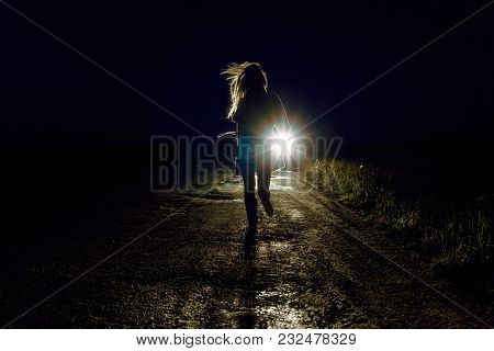 Running Female Silhouette On A Night Country Road Running Away From Pursuers By Car In The Light Of