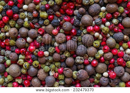 Black, Green, Pink, White And Fragrant Pepper Grains Mix Background Surface