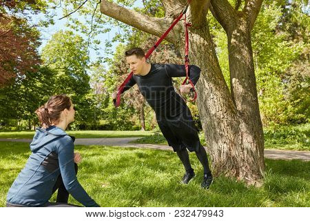 Suspension training in the park with personal fitness trainer