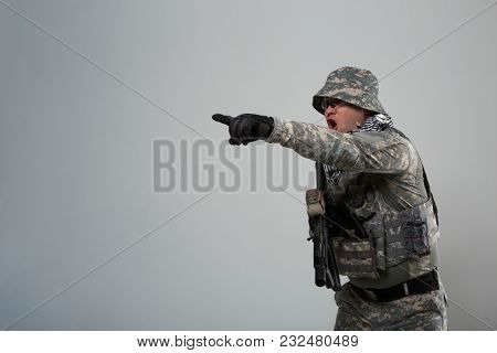 Picture of military man in helmet with hand pointing to side