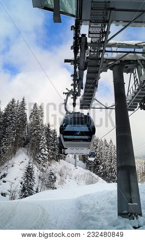 Zell Am See, Austria - February 14, 2018: Ski Lift. A Gondola Lift Enters The Station To Take Skiers