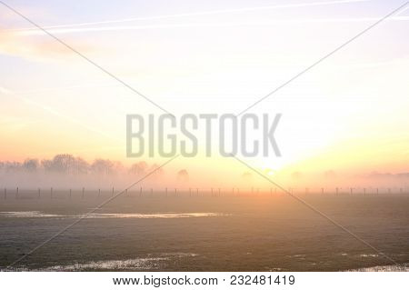 Natural Sunset Or Sunrise Over A Field Or Meadow With A Bright And Dramatic Sky And Dark Ground At T