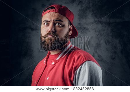 Portrait Of Serious, Bearded Male In Hip Hop Clothes On A Grey Background.