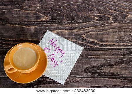 On A Wooden Background There Is A Cup Of Coffee Beside A Napkin With A Wish. Valentine's Day Concept