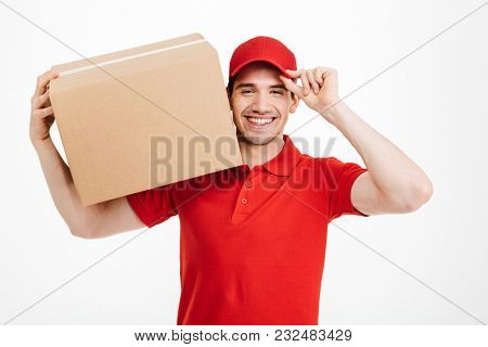Image of a handsome smiling young delivery man in red cap standing with parcel post box isolated over white background. Looking camera.