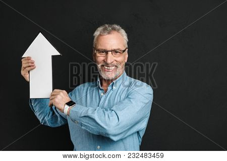 Photo of content elderly man 60s with grey hair and beard wearing glasses holding blank speech arrow pointer directing upward isolated over black background