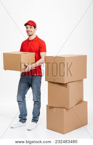 Image of a handsome smiling young delivery man in red cap standing with parcel post boxes isolated over white background. Looking aside.