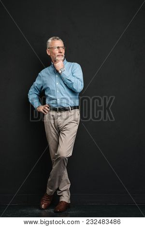 Full length photo of intelligent man 70s with grey hair and beard in classic wear looking aside with smile and pensive gaze isolated over black background