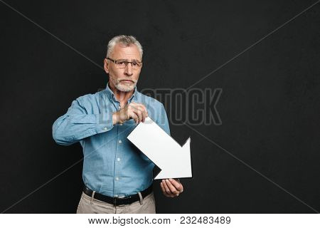 Image of frustrated bearded gentleman 60s with grey hair wearing eyeglasses holding blank speech arrow pointer directing downward isolated over black background