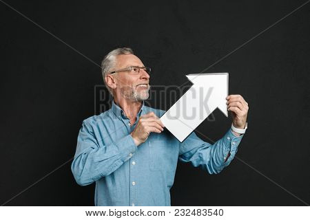 Photo of bearded gentleman 60s with grey hair wearing eyeglasses holding blank speech arrow pointer directing aside isolated over black background