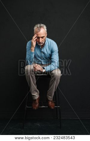 Full length photo of caucasian male pensioner 60s with short grey hair sitting on chair and looking down with brooding or uptight view isolated over black background