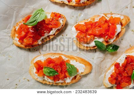 Italian Bruschetta On A Wooden Board With Feta Cheese And Herbs