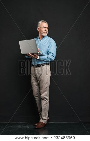 Full length photo of elderly businessman 70s with grey hair and beard looking aside while working on silver notebook in office isolated over black background