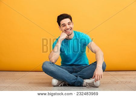 Portrait of a smiling young man looking at camera while sitting on a floor isolated over yellow background