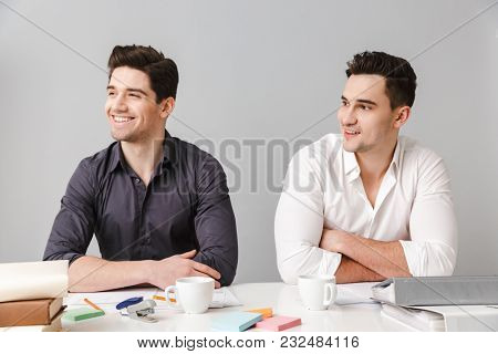 Image of handsome two smiling young business men colleagues sitting isolated over grey wall at the table coworking. Looking aside.