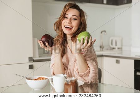 Portrait of a happy young woman having healthy breakfast while sitting at the table in a kitchen at home in the morning