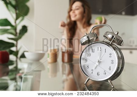 Close up of a satisfied young woman having healthy breakfast while sitting at the table with alarm clock in a kitchen at home in the morning