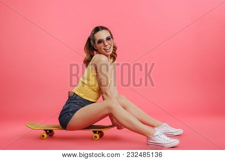 Full length portrait of a happy young girl dressed in summer clothes sitting on a skateboard isolated over pink background