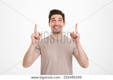 Positive brunette man 30s wearing beige t-shirt gesturing fingers upward on copyspace text or product isolated over white background