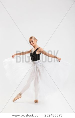 Picture of cheerful young woman ballerina dancing gracefully over white wall background isolated. Looking camera.
