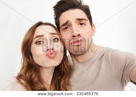 Closeup picture of amusing couple in relationship looking on camera and blowing air kiss while photographing themselves isolated over white background
