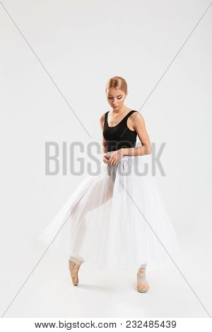 Image of cute young woman ballerina dancing gracefully over white wall background isolated. Looking aside.