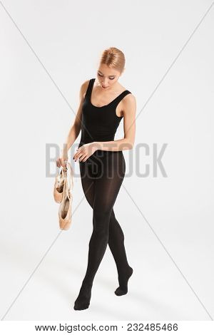 Picture of amazing young woman ballerina over white wall background isolated. Looking aside holding pointes.