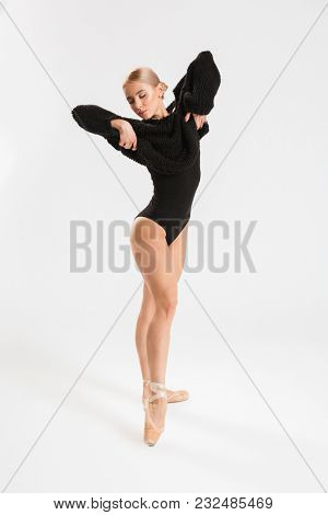 Picture of a beautiful young woman ballerina dancing gracefully over white wall background isolated. Looking aside.
