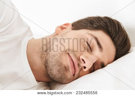 Close up smiling young man sleeping in bed