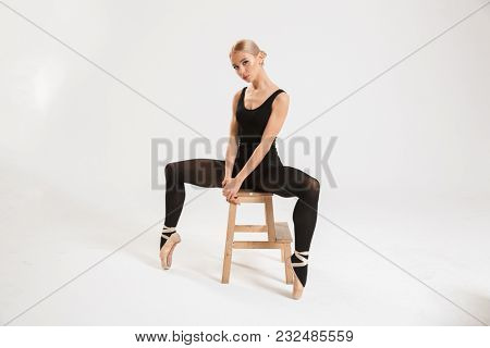 Picture of a beautiful young lady ballerina sitting over white wall background isolated. Looking camera.